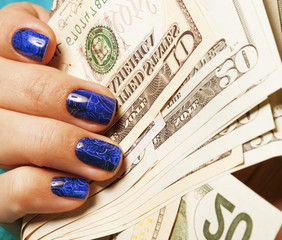 close up fingers with blue manicure holding dollars