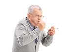 Senior smoking a cigar and coughing