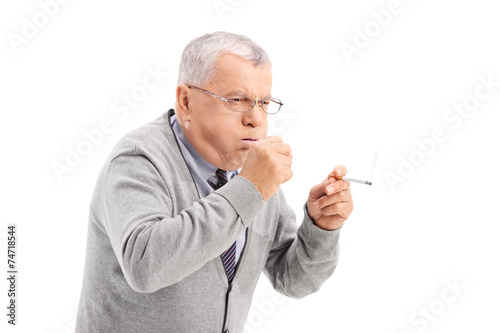 Senior smoking a cigar and coughing - 74718544