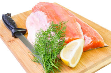 Composition of trout fish fillet with knife on a kitchen board