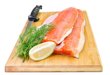 Rainbow trout fish fillet with knife on a kitchen board