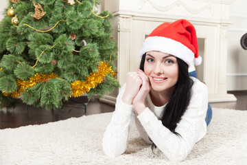 Cheerful seductive blonde woman lying on carpet at Christmas