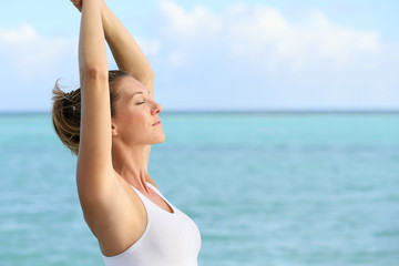 Portrait of fitness woman stretching out by the sea