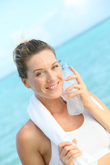 Portrait of fitness woman drinking water after working out