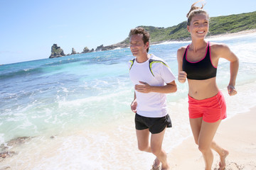 Couple runners exercising on a sandy beach
