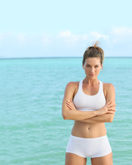 Portrait of beautiful fitness girl standing by the sea
