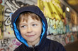young boy in front of a colorful graffiti wall