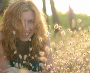 Portrait of a beautiful red-haired laughing girl in the grass
