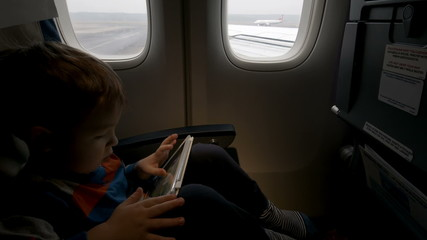 Boy using tablet PC in plane going to take off