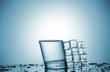 Water in glass and ice cubes, lying next