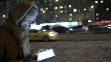 Woman typing message on pad while walking in the evening