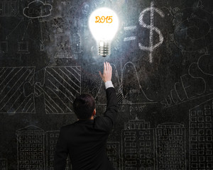 businessman touching 2015 light bulb illuminated dark doodles wa