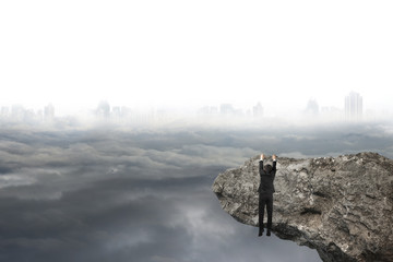 man hand hanging on cliff with gray cloudy sky cityscape