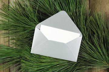 open silver envelope on fir tree