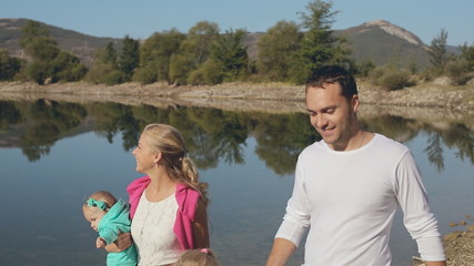 Lovely family with two daughters walking near water