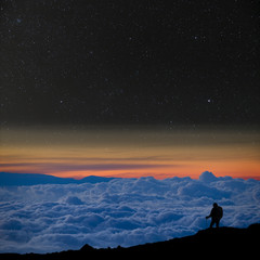 Lone climber above the clouds, looks at the starry night sky.