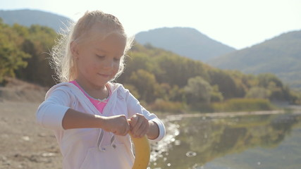 A cute little blonde girl standing on the shore of the lake and