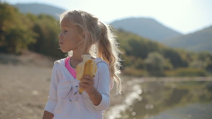 Amazing little girl eating a banana near the lake next to the