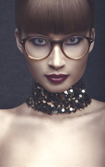 Portrait of a young woman with eye glases, and necklace