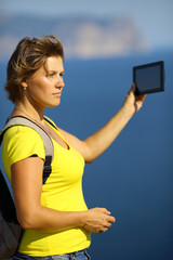 woman with tablet computer on the coast