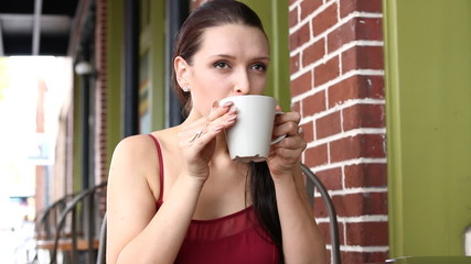 Happy young Latvian woman drinking latte at street cafe