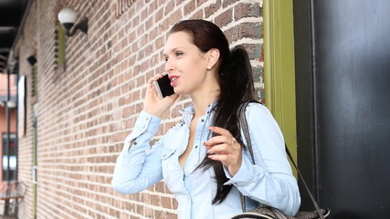 Happy young Latvian woman on mobile phone talking