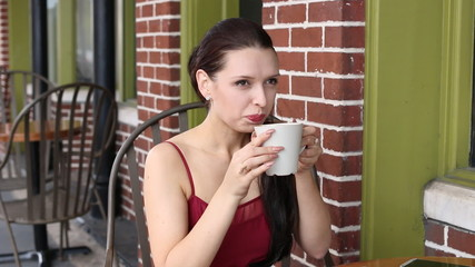 Beautiful happy Latvian woman drinking at cafe and smiling