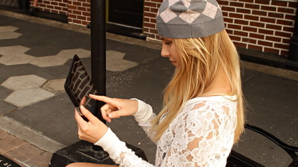 Pretty hipster young woman using tablet in city