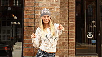 Hipster young woman on street making fun hand signs