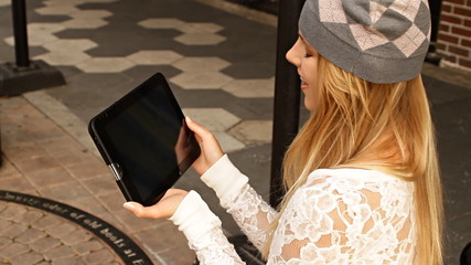 Pretty young hipster woman with digital tablet on street