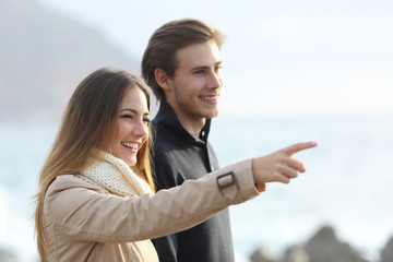 Couple looking forward on the beach and pointing