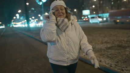 Woman having exciting phone talk during evening walk in city