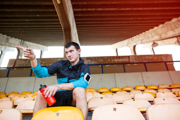 sportsman sitting with bottle of water on the stadium