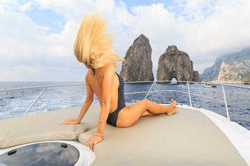 Young sexy woman enjoying on yacht at  island capri italy
