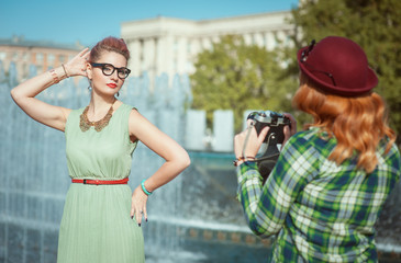 Two beautiful hipster girls taking pictures on an old camera