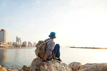 traveler with backpack sitting on the rocks