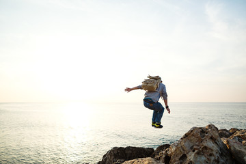 brave traveler with backpack jumping over the rocks near the sea