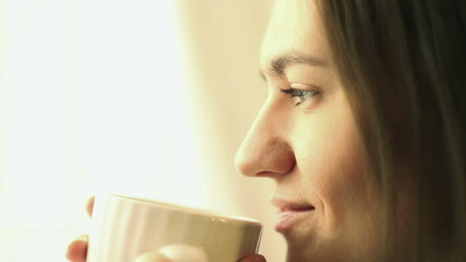Beautiful girl drinking tea or coffee, close up
