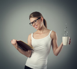Cheerful female reading book holding aromatic cup of coffee