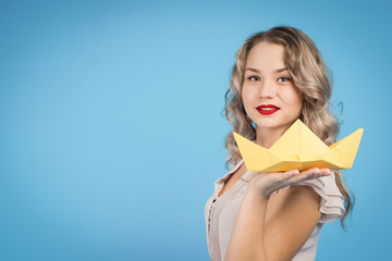 girl holding a paper boat
