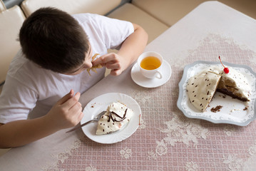 Boy drinks tea with cake at  table