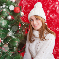 Beautiful young woman  near Christmas tree