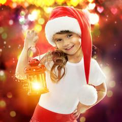 Little girl in Santa hat holding red Christmas lantern