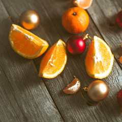 Tangerines, oranges and Christmas decorations on a wooden table