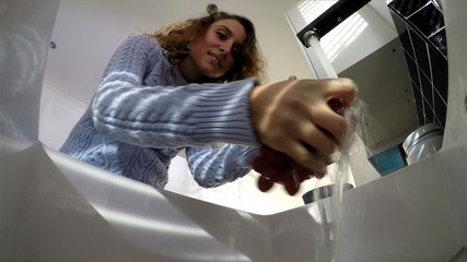 Attractive woman washing grapes in a kitchen sink
