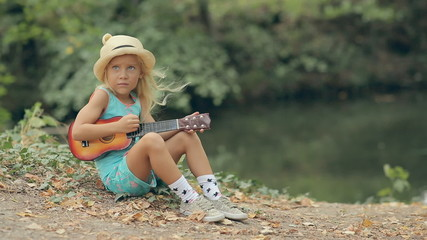 Little blond girl in a straw hat sitting near the river and
