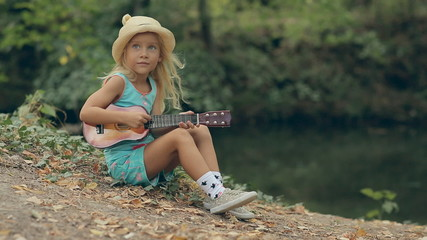 Amazing little girl with straw hat sitting by the river and