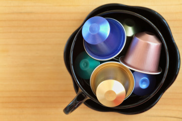 Overhead view of coffee cup filled with coffee capsules