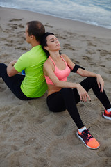 Fitness couple resting after workout sitting on the beach, exhau