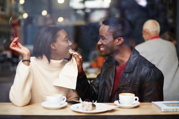 Young couple in love having fun drinking coffee in cafe